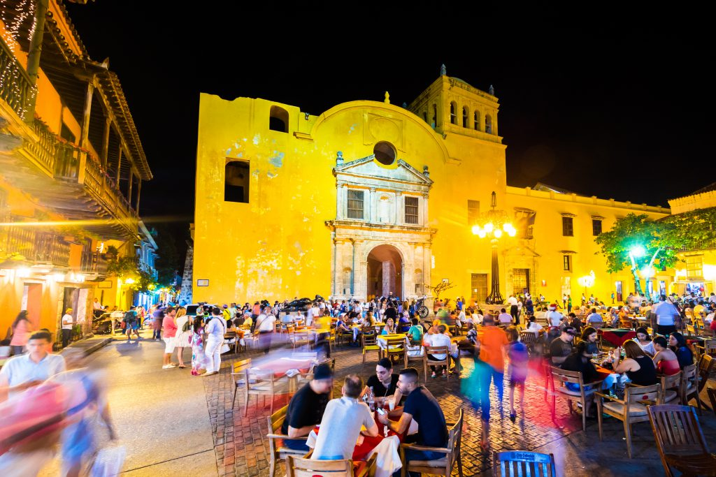 Cartagena, Colombia - December 19, 2014: People fillip up the seats in Plaza Santo Domingo, a plaza popular among locals and tourists in Cartagena, Colombia.